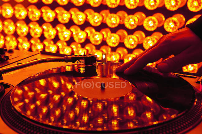 Crop DJ hand scratching record at turntable — Stock Photo