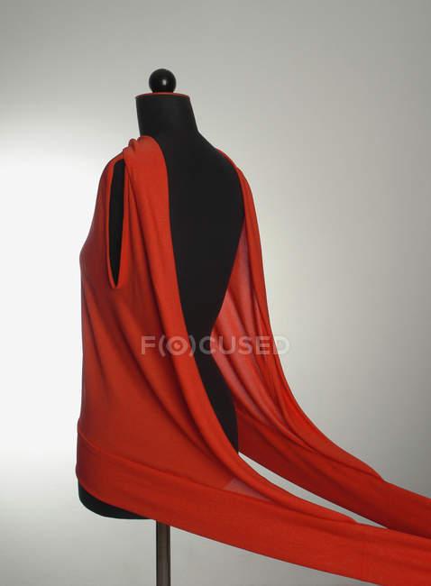 Rouge vêtement sur mannequin de couture sur fond gris — Photo de stock