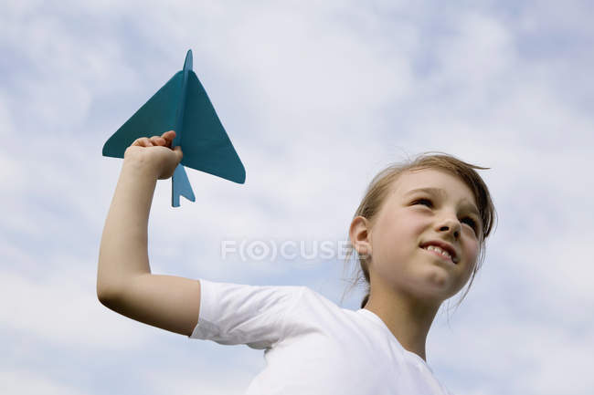 A young girl holding a model airplane — Stock Photo
