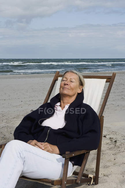 Senior woman reclining in lounge chair on the beach — Stock Photo