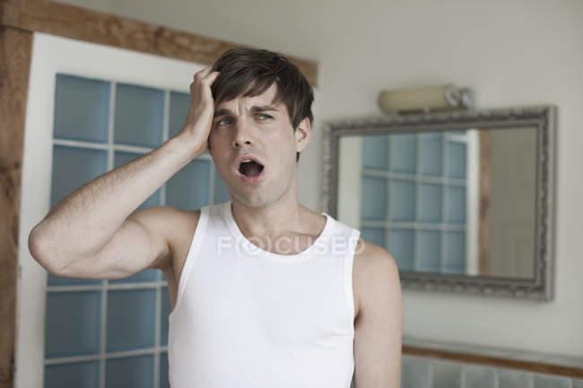 Uomo stanco con mano nei capelli sbadigliare in bagno — Foto stock