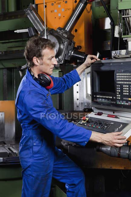 Человек, управляющий машиной на заводе металлических деталей — стоковое фото