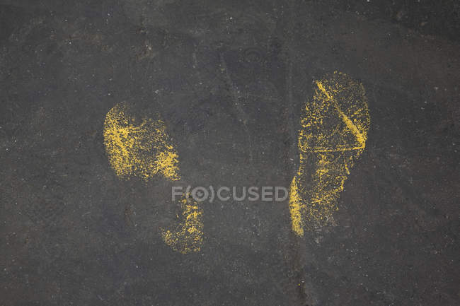 Yellow footprints in paint on asphalt — Stock Photo