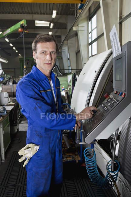 Портрет человека, управляющего машиной на заводе — стоковое фото