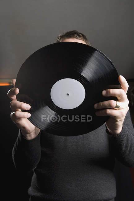 Man holding record in front of face — Stock Photo