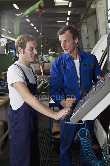 Два ручных рабочих разговаривают и работают на заводе металлических деталей — стоковое фото
