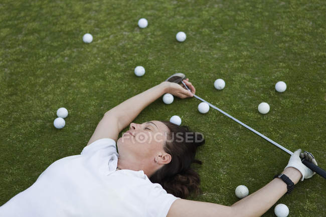 An exhausted golfer lying down on a golf course — Stock Photo
