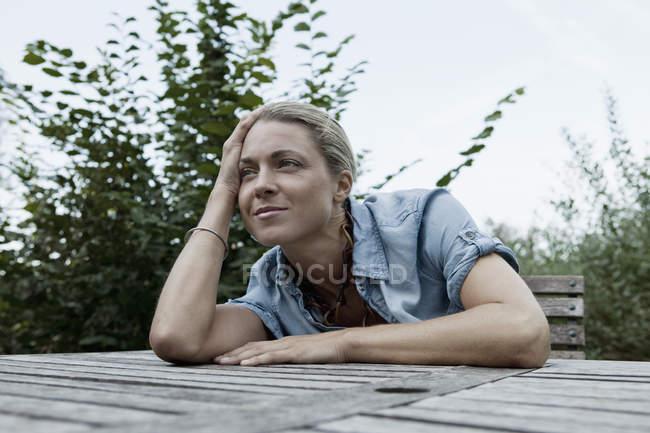 Une femme assise à une table en plein air, scène non urbains — Photo de stock
