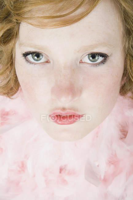 Um retrato de uma jovem mulher usando uma boa pena rosa — Fotografia de Stock