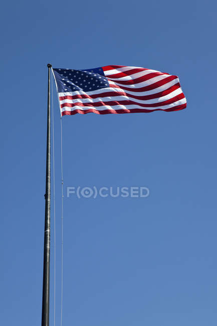American flag waving over clear blue sky — Stock Photo
