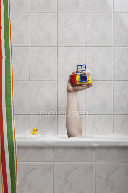 Crop hand sticking out of bathtub holding underwater camera — Stock Photo