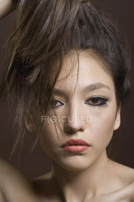 Portrait d'adolescente brandissant ses cheveux sur fond marron — Photo de stock