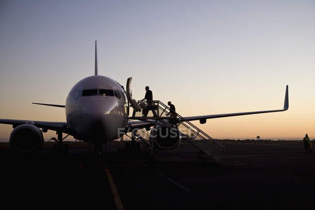 Silhouettes de personnes embarquant dans l'avion à l'aéroport au crépuscule — Photo de stock