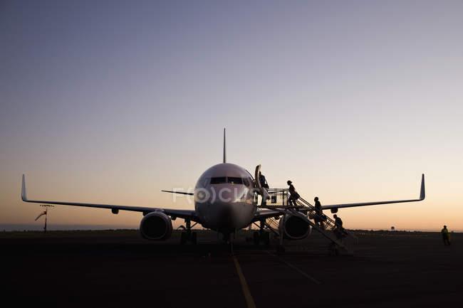 Silueta de personas abordar avión al atardecer - foto de stock
