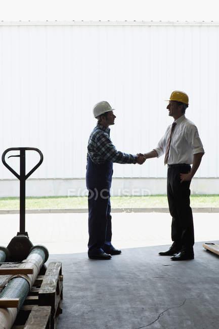 Handarbeiter beim Händeschütteln mit einem Manager in einem Metallteilelager — Stockfoto