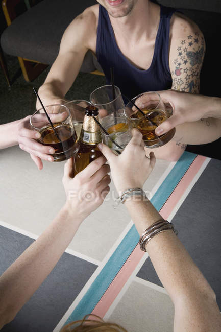 A group of friends toasting drinks at a bar — Stock Photo