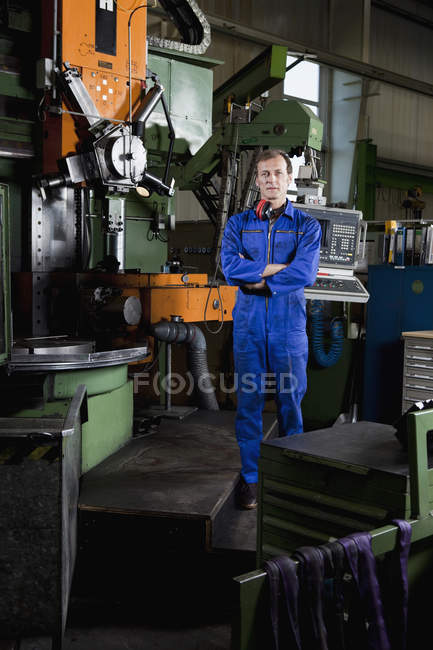 Portrait of a worker standing in a metal parts factory — Stock Photo