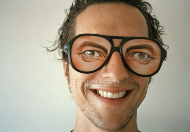 A man wearing novelty glasses and smiling — Stock Photo