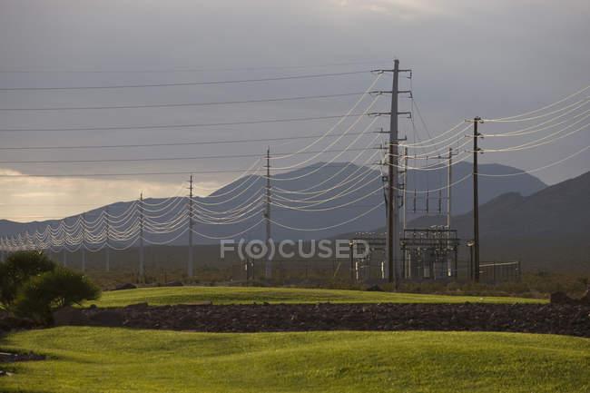Lignes électriques dans plus de montagne au crépuscule — Photo de stock