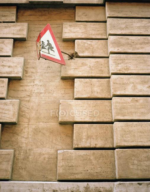 Mauer mit verbogenem Verkehrsschild für Schulweg — Stockfoto