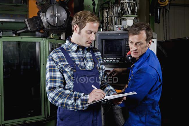 Двое мужчин на заводе металлических деталей просматривают буфер обмена — стоковое фото