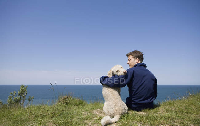 Un uomo con il braccio intorno a un cane seduto in riva al mare — Foto stock