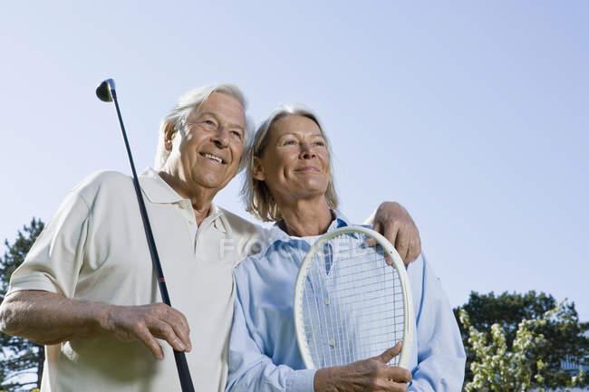 Coppia anziana che tiene golf club e racchetta da tennis — Foto stock
