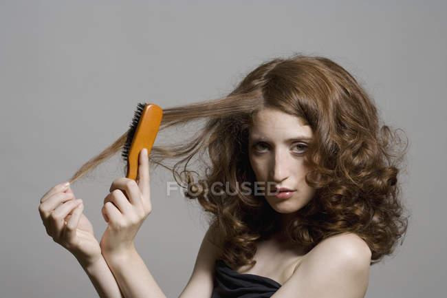 Portrait de jeune femme se brosser ses cheveux sur fond gris — Photo de stock