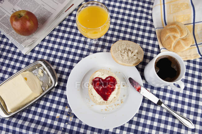 Top view of breakfast table with heart shaped jam on sandwich — Stock Photo