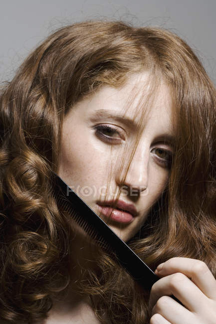 Portrait d'une jeune femme peignant ses cheveux — Photo de stock
