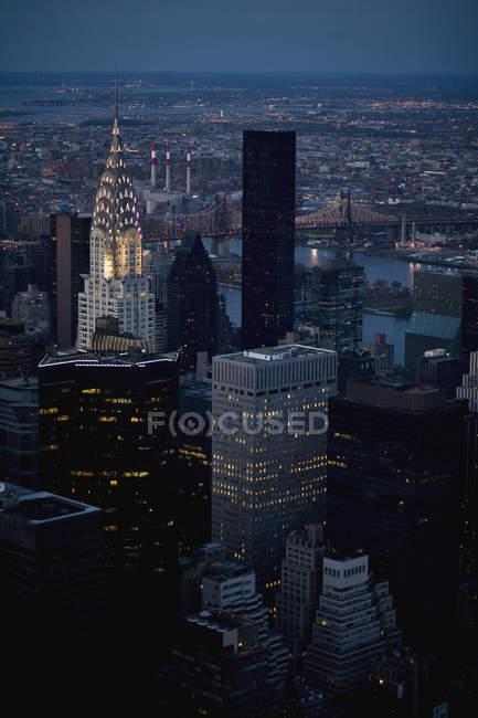 Vista aérea de las fachadas de rascacielos en el paisaje urbano en la noche - foto de stock