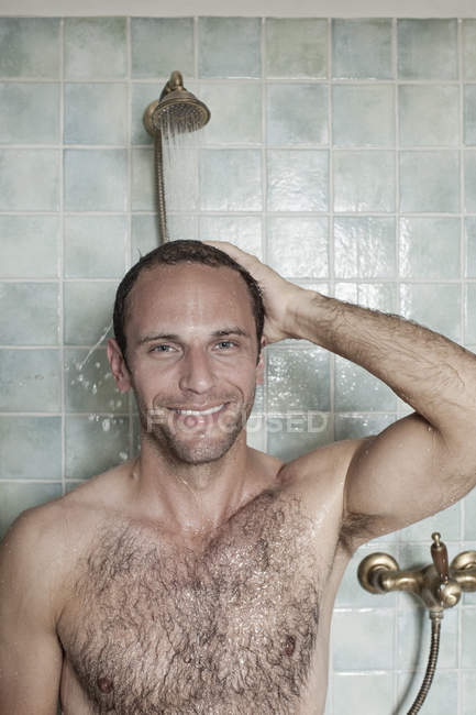 Portrait of smiling shirtless man taking shower in front of tiled wall — Stock Photo