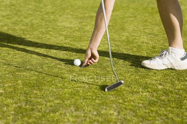 Unterteil des Golfers markiert Ballposition mit Münze auf Golfplatz — Stockfoto
