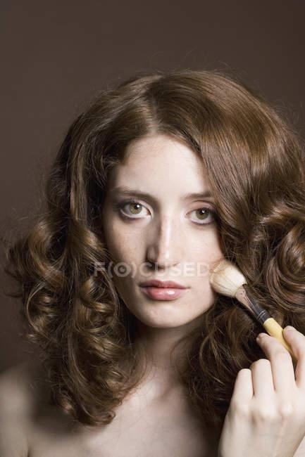 Portrait d'une jeune femme, appliquer la poudre pour le visage — Photo de stock