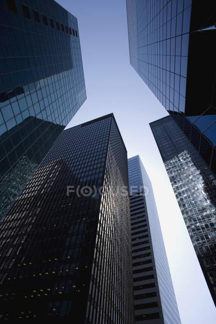 Vista de ángulo bajo de rascacielos en el distrito financiero, Manhattan, Nueva York - foto de stock