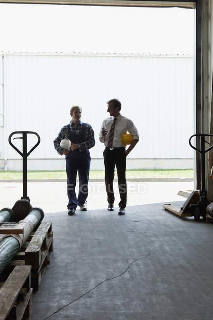 Manager im Gespräch mit einem Arbeiter beim Gang in die Lagerhalle — Stockfoto