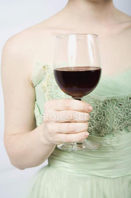 Mittelteil der Frau trägt Vintage-Kleid und hält ein Glas Rotwein in der Hand — Stockfoto