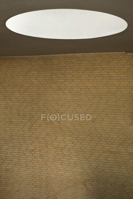 Luz oval en techo sobre pared de ladrillo en blanco - foto de stock