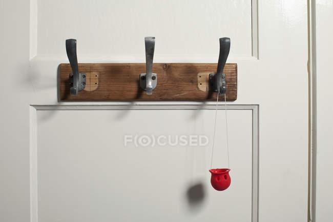 Red clown's nose hanging from coat hook on door — Stock Photo