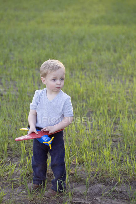 A portrait of a young boy holding a toy airplane, outdoors — Stock Photo