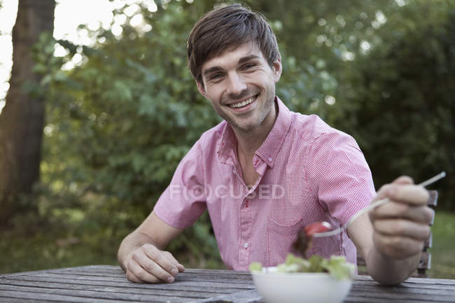 Мужчина ест за столом на открытом воздухе, вне городской сцены — стоковое фото