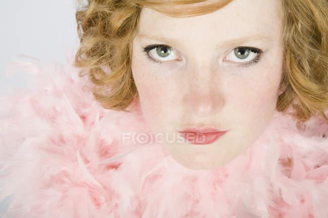 Ritratto di una giovane donna che indossa un boa di piuma rosa — Foto stock