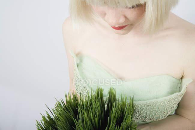 Eine junge Frau mit einer Weizengraspflanze — Stockfoto