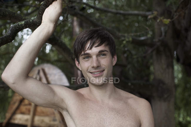 Wet man holding onto branch and hot tub on background — Stock Photo