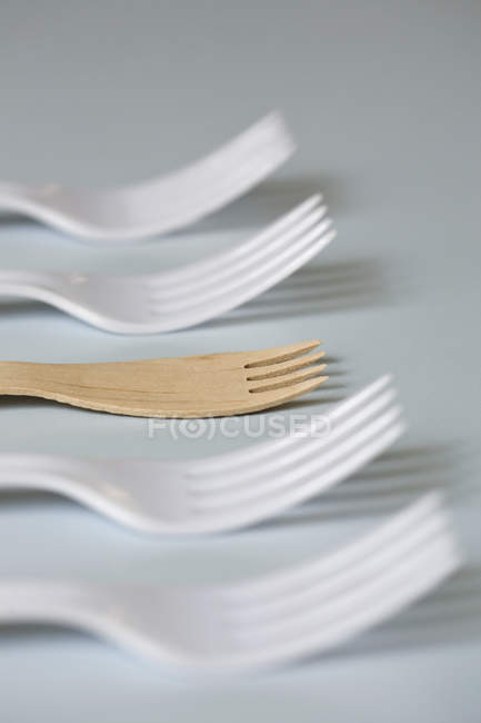 Row of four plastic forks and one wooden fork on table — Stock Photo