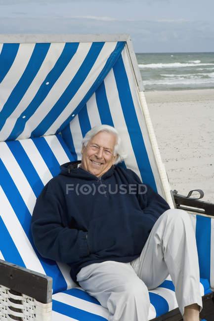 Porträt eines älteren Mannes, der auf einem Strandkorb mit Kapuze sitzt — Stockfoto