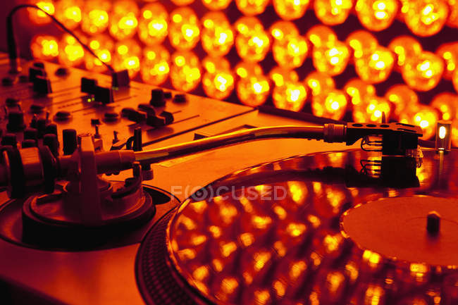 Close up view of turntable and sound mixer illuminated by lighting equipment — Stock Photo
