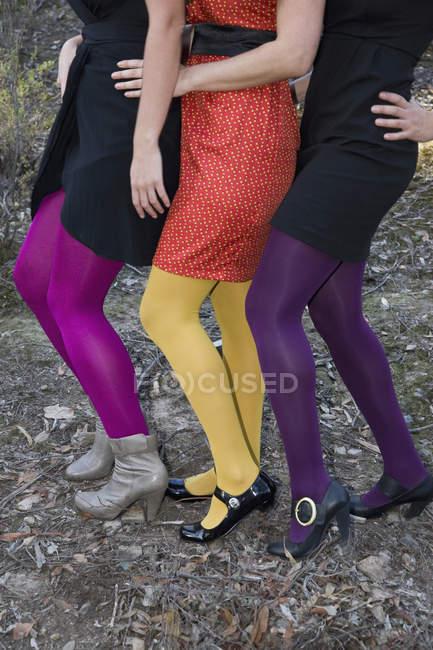 Vue de la taille vers le bas de trois femmes habillées en vêtements de fête — Photo de stock