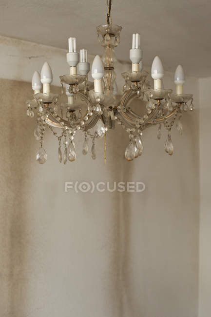 Old and dirty chandelier hanging in bare room — Stock Photo