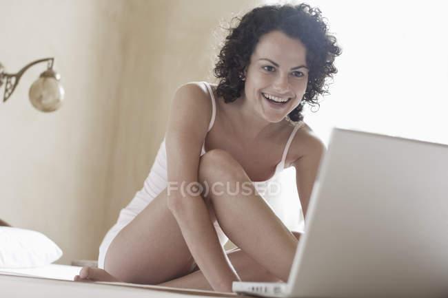 Donna eccitata seduta sul letto e utilizzando il computer portatile — Foto stock